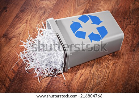 Flipped recycle bin full of shredded paper on a wooden floor - stock photo