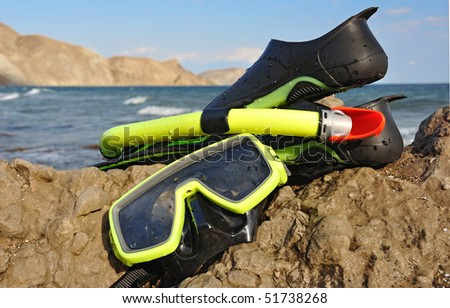 Flippers, snorkel and diving mask on seacoast.