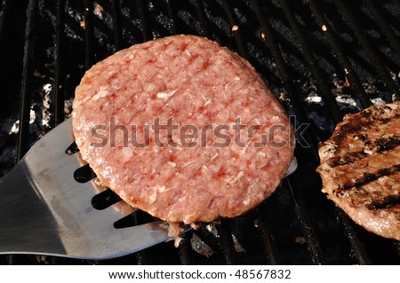 Flipping Hamburgers on the Grill with a Spatula - stock photo