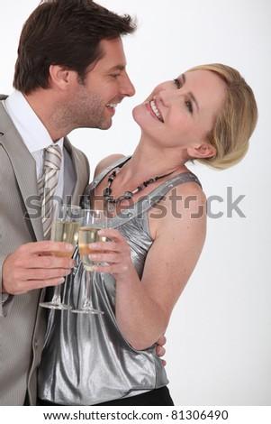 Flirtatious man and woman drinking champagne - stock photo