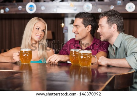 Flirting at the bar. Two cheerful young men and beautiful young women talking at the bar and drinking beer - stock photo