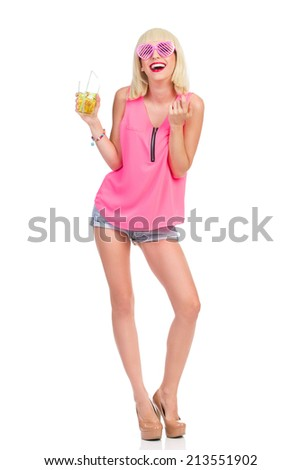 Flirting at the party. Blonde young woman in high heels, pink top and jeans shorts holding lime drink and beckoning. Full length studio shot isolated on white. - stock photo