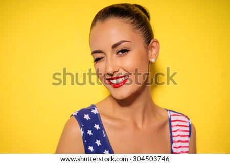 Flirting beauty. Bright studio portrait of young pretty brunette woman winking and smiling. Yellow background. - stock photo