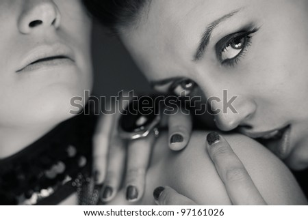 Flirting girl's couple over dark gray background. Black and white