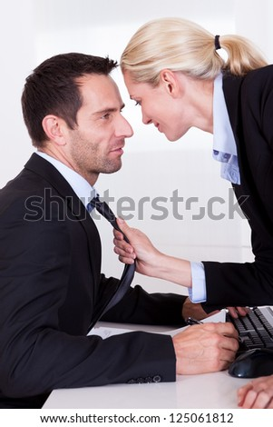 Flirting in the office as a beautiful blonde businesswoman pulls a colleague towards her by his tie - stock photo