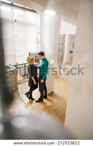 Flirting stylish young couple in their appartment. The foreground is blurred, the focus is on the couple in the middle of the frame. - stock photo