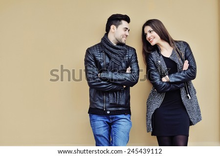 Flirting young couple standing near a wall and looking to each other smiling  - stock photo