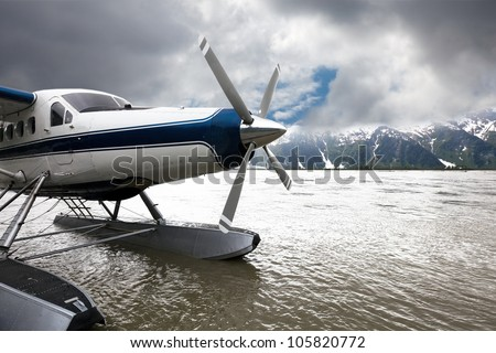 Float plane or seaplane in Alaska that has landed with storm clouds overhead.  The blue and white plane flew from Juneau. - stock photo