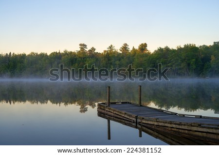Floating boat dock with a calm early morning mist hanging above the water and the sun just touching the tops of the forest and trees at Toddy Pond, Maine. - stock photo
