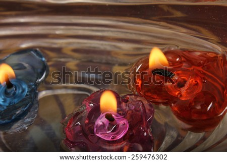 floating burning candles in glass aroma bowl - stock photo