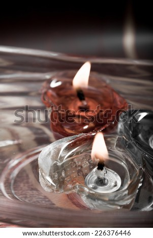 floating burning candles in glass aroma bowl - vintage - stock photo