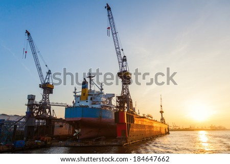floating dock with a container ship in the harbour - stock photo