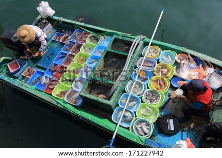 Floating Fish Market. Unusual assortment of fresh fish for sale. One of the fisherman is taking a lunch break. - stock photo