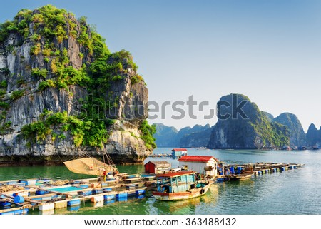 Floating fishing village in the Halong Bay (Descending Dragon) at the Gulf of Tonkin of the South China Sea, Vietnam. Landscape formed by karst towers-isles in various sizes. Blue sky in background. - stock photo