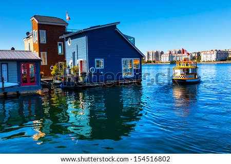 Floating Home Village Blue Houseboats Water Taxi Fisherman's Wharf Reflection Inner Harbor, Victoria British Columbia Canada Pacific Northwest.  Area has floating homes, piers, restaurants.  - stock photo