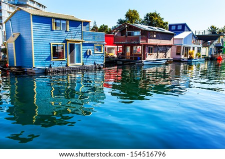 Floating Home Village Blue Red Brown Houseboats Fisherman's Wharf Reflection Inner Harbor, Victoria British Columbia Canada Pacific Northwest.  Area has floating homes, boats, piers, and restaurants.  - stock photo