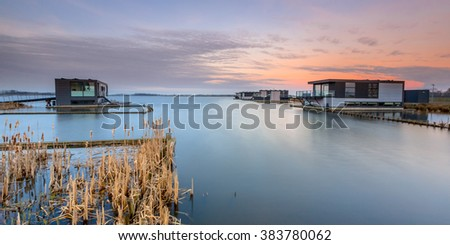 Floating houses on a tranquil lake at sunset in Groningen, the Netherlands
