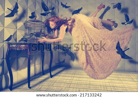 Floating Levitation shot of a Woman and Her Black Birds - stock photo