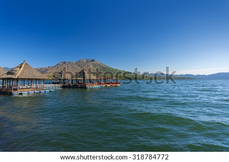 floating restaurant at batur lake with blue sky, bali indonesia - stock photo