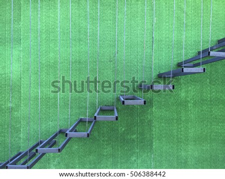 Floating steel staircase on a building green wall.