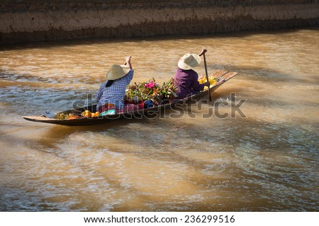 Floating vendors on small  long wooden boat  with fresh vegetables and flowers row at dark water - stock photo