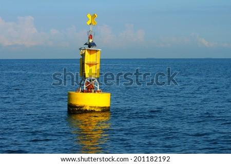 Floating yellow navigational buoy on blue sea - stock photo