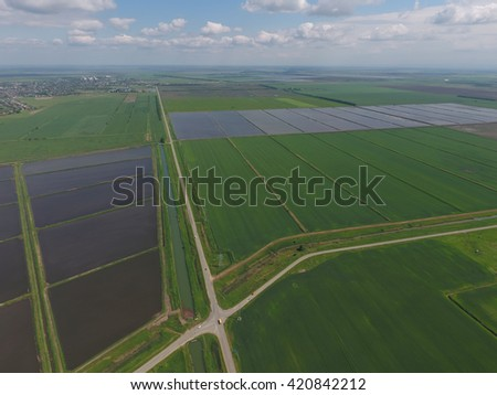Flooded rice paddies. Agronomic methods of growing rice in the fields. Flooding the fields with water in which rice sown. View from above. - stock photo