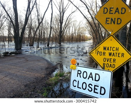 Flooded road with warning signs - stock photo