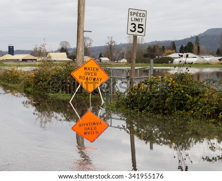 Flooded road with water over roadway sign - stock photo
