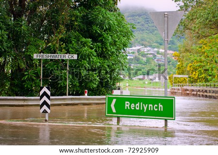 Flooded roundabout, road signs and bridge in Queensland, Australia after heavy rain