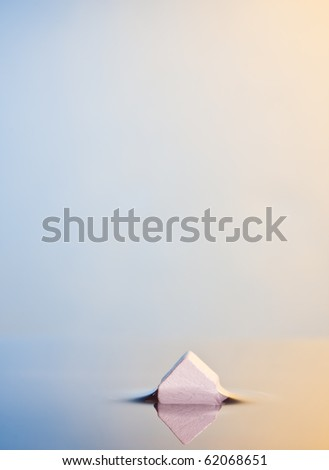Flooding or bankruptcy Concept. Abstract Macro of a little white house in calm water. Background with ample space for copy. - stock photo