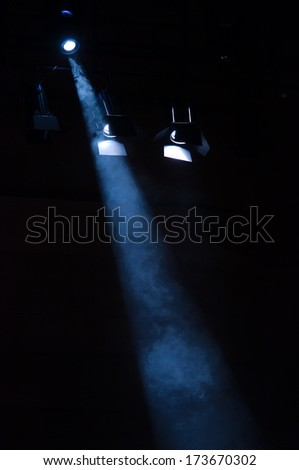 Floodlight goes trough smoke on dark background