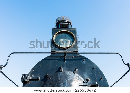 Floodlight or projector of an ancient steam locomotive. Petroleum lamp and a metal reflector inside the metal cage. Black boiler to the fore. Horizontal, landscape orientation photography - stock photo