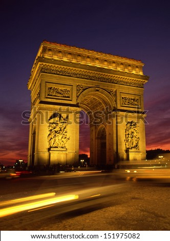 Floodlit Arc De Triomphe Paris and the Place Charles de Gaulle with traffic trails and sunset - stock photo