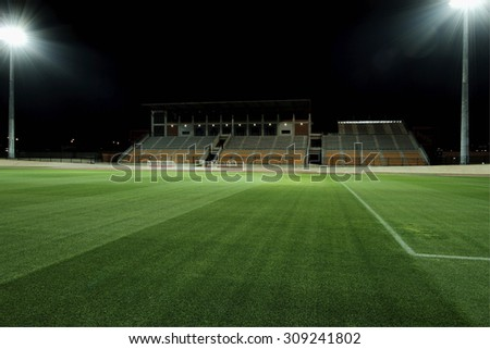 floodlit sports stadium with freshly cut grass and bright flood lights  - stock photo