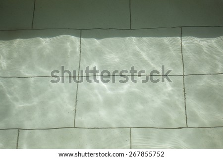 Floor pool under water. Bottom of the pool, consisting of ceramic tiles, which is under water. Image contains shades of gray and green. - stock photo