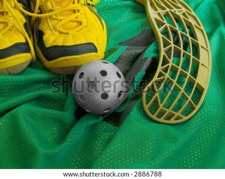 Floorball ball, stick, and shoes on a green jersey. - stock photo