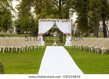 floral arch in the park chairs on the grass wedding banquet