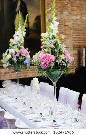 Floral arrangement at wedding reception with pink, purple and white flowers