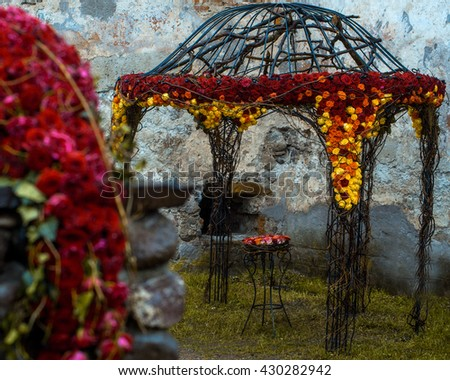 Floral arrangement with colorful rose flowers and wooden twigs on open garden house near old white building