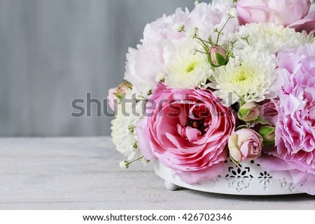 Floral arrangement with pink peonies, tiny roses, chrysanthemums and gypsophila paniculata twigs, copy space. - stock photo