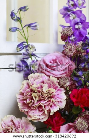 Floral arrangement with pink roses, carnations and delphinium flowers.