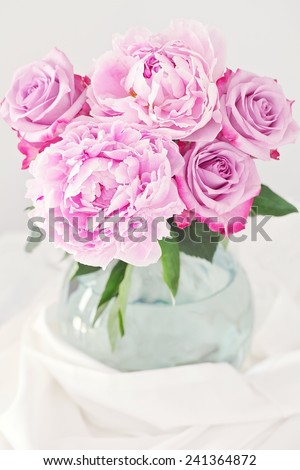 Floral composition with a pink peony and roses in a glass vase.