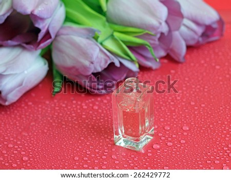 Floral perfume bottle on background of purple tulips - stock photo