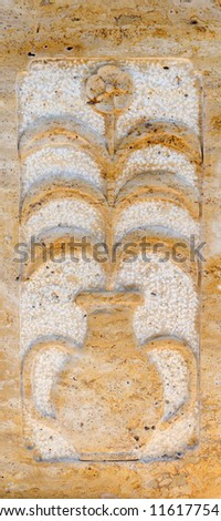 Floral stone decorative panel on a wall depicting a flowering plant in a two handled amphora