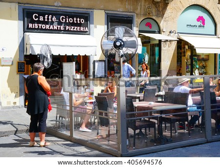 FLORENCE, ITALY - AUGUST 22, 2014: People sitting by tables of a Caffe Giotto restaurant on the city center - stock photo