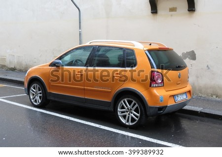 FLORENCE; ITALY - CIRCA JANUARY 2016: orange Volkswagen Polo car parked in a street of the city centre. - stock photo