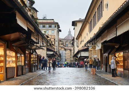Florence, Italy - Febuary 17, 2016: Street View of Ponte Vecchio, a medieval stone bridge over the Arno River in Florence. It is famous for still having shops built alog the bridge. - stock photo