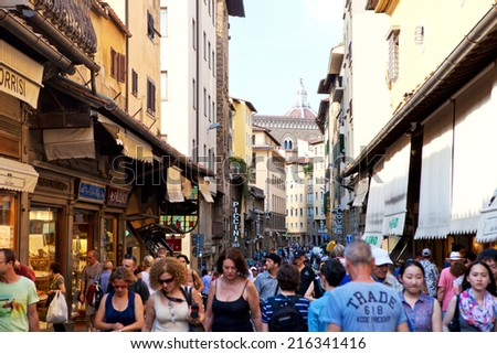 FLORENCE, ITALY - JUNE 12: Tourists walking by The Ponte Vecchio in Florence, Italy on June 12, 2014. It is a Medieval stone closed-spandrel segmental arch bridge over the Arno River. - stock photo