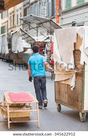 Florence, Italy-June 2, 2015. Workers pulling packed up stalls into the famous San Lorenzo outdoor leather market during the early morning set up of the market stalls - stock photo